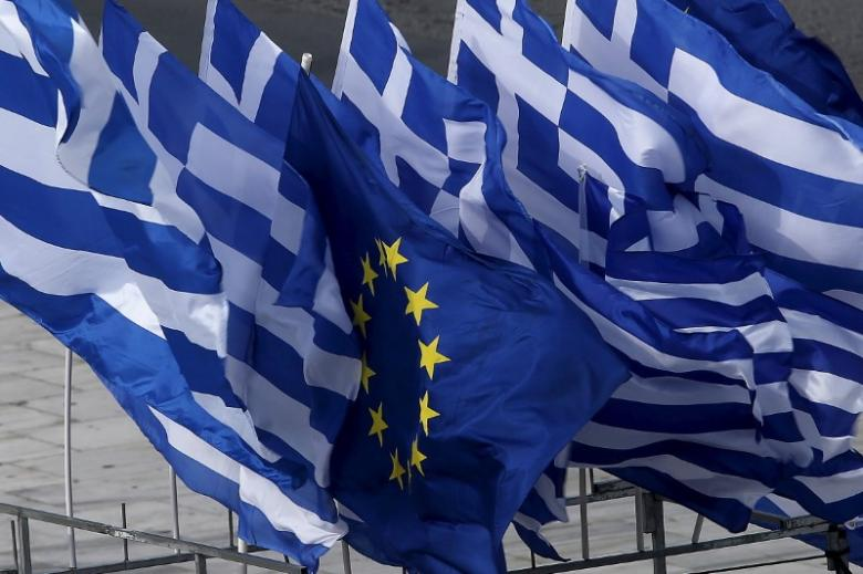 Greek and EU flags flutter at a open-air kiosk in Athens