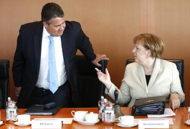 German Chancellor Merkel talks with Economy Minister Gabriel during the weekly cabinet meeting at the Chancellery in Berlin